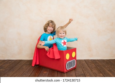 Superheroes children playing in cardboard box. Kids having fun at home. Childhood dream and imagination concept