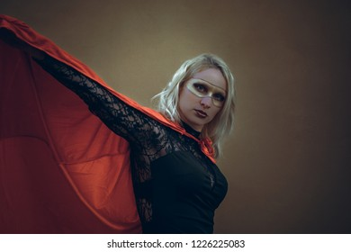 superheroine with red cape in front of a brown wall
