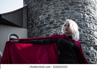 Superheroine with red cape in front of a tower
