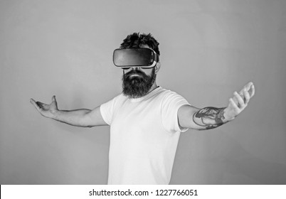 Superiority concept. Hipster on serious face raising hands while enjoy superiority in virtual reality. Guy with head mounted display interact in VR. Man with beard in VR glasses, green background.