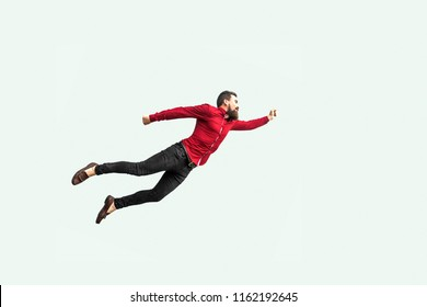 superman flying. Enthusiasm concept. strong bearded businessman in red shirt  felt himself a superhero or super man and flying up. indoor studio shot isolated on gray background.