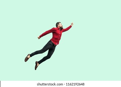 superman flying. Enthusiasm concept. strong bearded businessman felt himself a superhero or super man and flying up. indoor studio shot isolated on light green background.