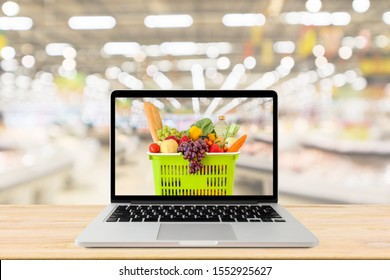 supermarket aisle blurred background with laptop computer and shopping basket on wood table grocery online concept