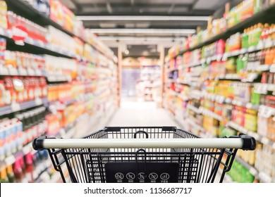 Supermarket aisle with empty black shopping cart