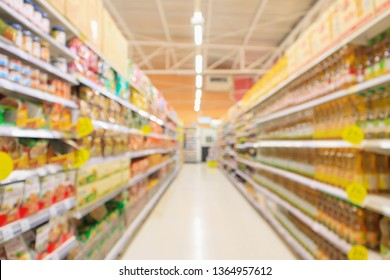 supermarket aisle with seasoning and cooking vegetable oil bottles product shelves interior defocused blur background