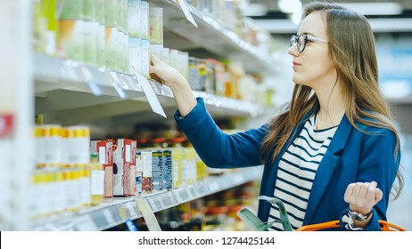 At the Supermarket: Beautiful Young Woman Browses through the Canned Goods Section of the Store. She Has Shopping Basket Full of Healthy Food Items.