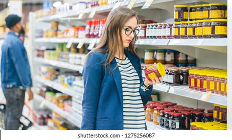 At the Supermarket: Beautiful Young Woman Browses through the Canned Goods Section of the Store. She Checks Nutritional Value of Strawberry Jam. She Has Shopping Basket Full of Healthy Food Items.