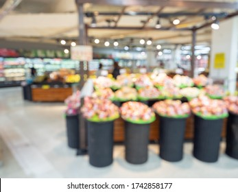 Supermarket blur background. Blurred interior view with fruit booth display in shopping mall.