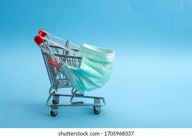 Supermarket cart for shopping. The trolley is wearing a medical mask. Coronavirus control concept. Creative idea for an online pharmacy, online drug sale.