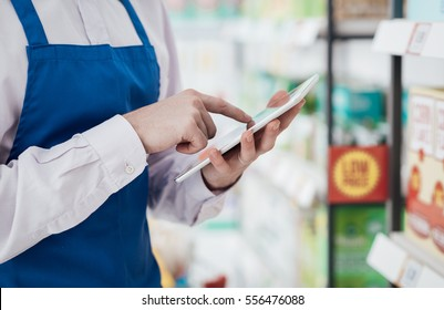 Supermarket clerk using apps on a digital tablet, innovative technology and work concept, hands close up