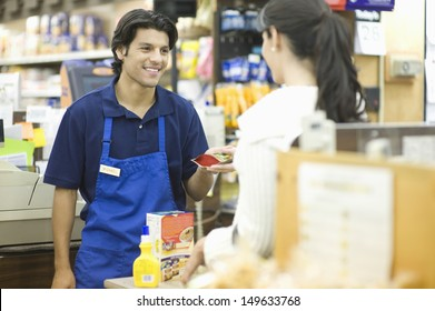 Supermarket employee in blue apron assisting female customer