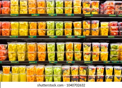 supermarket grocery display case with fresh cut fruit on shelves in plastic containers