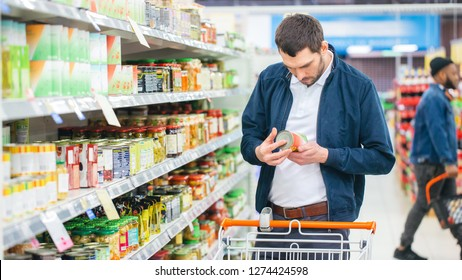 At the Supermarket: Handsome Man Uses Smartphone and Looks at Nutritional Value of the Canned Goods. He's Standing with Shopping Cart in Canned Goods Section.