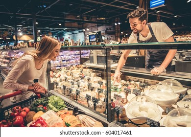 At the supermarket. Handsome worker is offering cheese to the beautiful customer and smiling