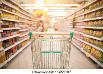 Supermarket interior, empty red shopping cart.
