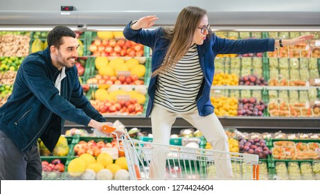 At the Supermarket: Man Pushes Shopping Cart with Woman Standing in it, Happy Couple Has Fun Racing / Surfing in a Trolley through the Fresh Produce Section of the Store.