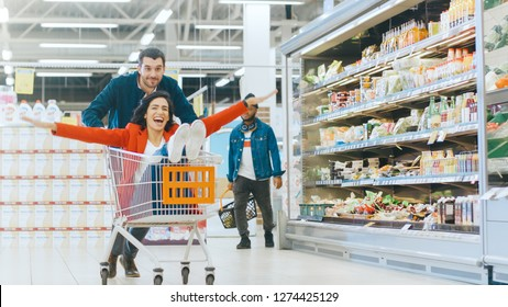 At the Supermarket: Man Pushes Shopping Cart with Woman Sitting in it, Happy Couple Has Fun Racing in a Trolley through the Fresh Produce Section of the Store.
