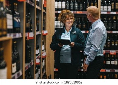 Supermarket manager discussing with connoisseur. Two people working in a winery store.