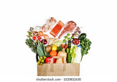 Supermarket. Paper bag full of healthy food on a white background. Top view. Flat lay