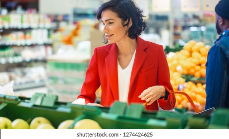 At the Supermarket: Portrait of the Beautiful Smiling Woman Choosing Organic Fruits In the Fresh Produce Aisle and Puts them into Shopping Basket.