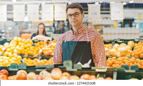 At the Supermarket: Portrait Of the Handsome Stock Clerk Wearing Apron, Arranging Organic Fruits and Vegetables, He Smiles into Camera. Friendly, Efficient Worker at the Store.