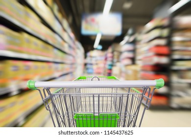 supermarket shelves aisle with shopping cart in motion defocused interior blur background