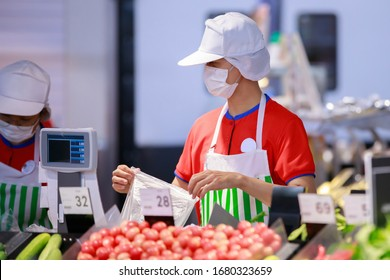 supermarket staff in medical protective mask working at supermarket.covid-19 spreading outbreak