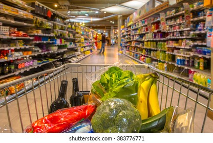 Supermarket trolley at an  aisle filled up with healthy vegetables seen from the consumers point of view from above