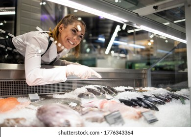 Supermarket worker arranging frozen fish for sale.Woman in working uniform selling fish in grocery store.