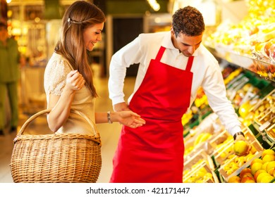 Supermarket worker helping customer to choose grocery