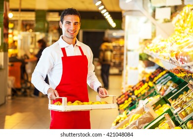 Supermarket worker standing by the grocery shelf an selecting goods