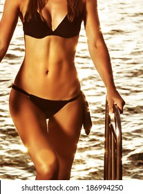 Supermodel on the beach, perfect slim body part, mild yellow sunset light, healthy lifestyle, summertime photo shoot concept
