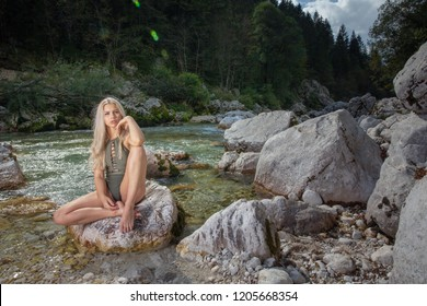 Supermodel woman posing in swimsuit sitting in the beautiful nature near the Soca river