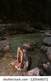 Supermodel woman posing in swimsuit sitting in the beautiful nature on the rock near the Soca river