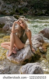 Supermodel woman posing in swimsuit sitting on the rock near the river
