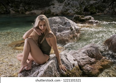 Supermodel woman posing in swimsuit sitting on the rock near the Soca river