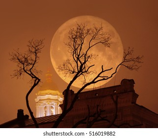 Supermoon with a church and a tree in foggy weather. Supermoon, a rare astronomical full moon phenomenon. Moon is bigger as normal in the sky. Mist, photo illustration with double exposure.