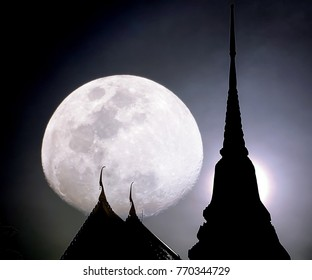 Supermoon over Buddhist temple and pagoda in Bangkok Thailand.    Photo taken in the night of 3 December 2017