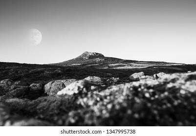 Supermoon over Carn Llidi peak seeing through rocky hinterland from St Davids Head in Pembrokeshire, UK. Black and white edit