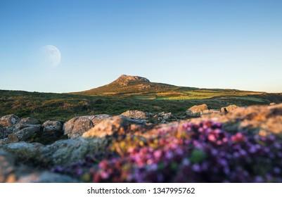 Supermoon over Carn Llidi peak seeing through rocky hinterland from St Davids Head in Pembrokeshire, UK