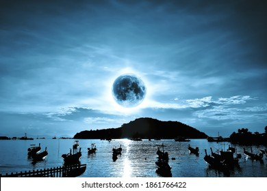Supermoon over island and sea in the night. Seaside with long tail boat and moonlight reflection on surface of sea. Imagination of tremendous moon over island. Elements of this image furnished by NASA