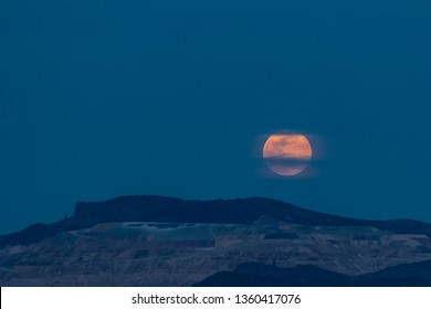 A supermoon rises over an iconic mountain in the southwest.