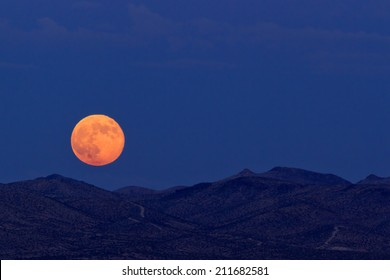 Supermoon rising over desert mountains in Barstow, California.