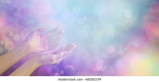 Supernatural Phenomenon - female healing hands gently cupped up facing towards an ethereal blue white light orb on a muted multicolored bokeh background with plenty of copy space