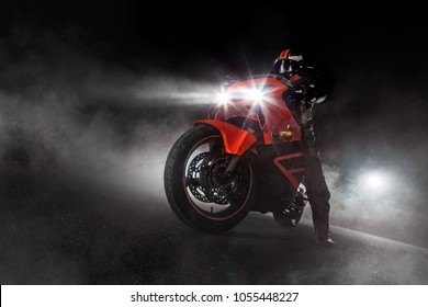 Supersport motorcycle driver at night with smoke around. Dark motorbike wallpaper