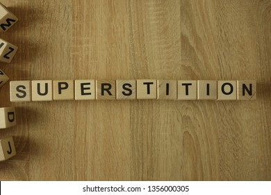 Superstition word from wooden blocks on desk