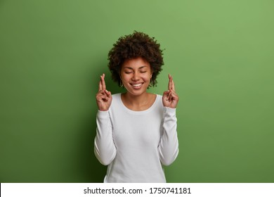 Superstitious hopeful woman with Afro hairstyle, smiles broadly, holds fingers crossed for dreams come true, makes wish and has faith in better life, wears white jumper, isolated on green background