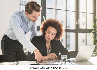 Supervisor checking business statistics and explaining the results to a colleague sitting at desk in the office