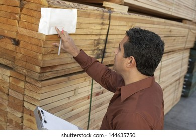 Supervisor checking label on stack of wood in warehouse