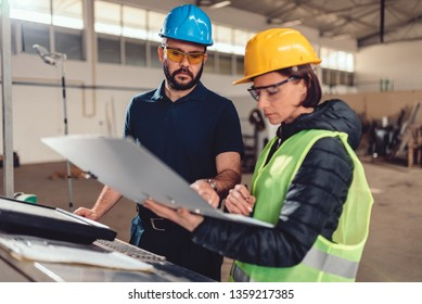 Supervisor checking production schedule with CNC machine operator in industrial factory